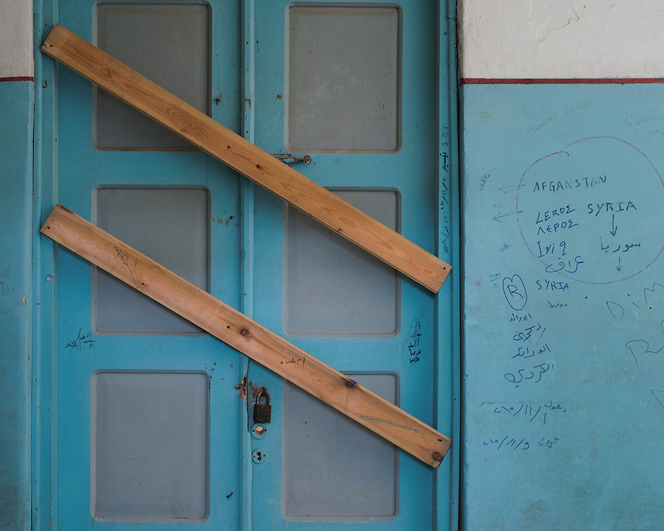 A boarded up door and graffiti at the closed down refugee camp at the Port of Lakki. <br />