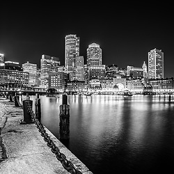 Boston skyline at night black and white picture with the Boston Harborwalk waterfront, downtown Boston skyscrapers and Nothern Avenue Bridge.