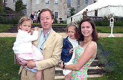 "Editor of Tatler GEORDIE GRIEG and his wife KATHERINE with their twin daughters, left OCTAVIA and right MONICA at a luncheon hosted by Cartier at the 2004 Goodwood Festival of Speed on 27th June 2004.  Cartier sponsored the ""Style Et Luxe' for vintage cars on the final day of this annual event at Goodwood House, West Sussex."