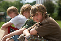 Three teenage brothers (13-17) sitting on street curb portrait