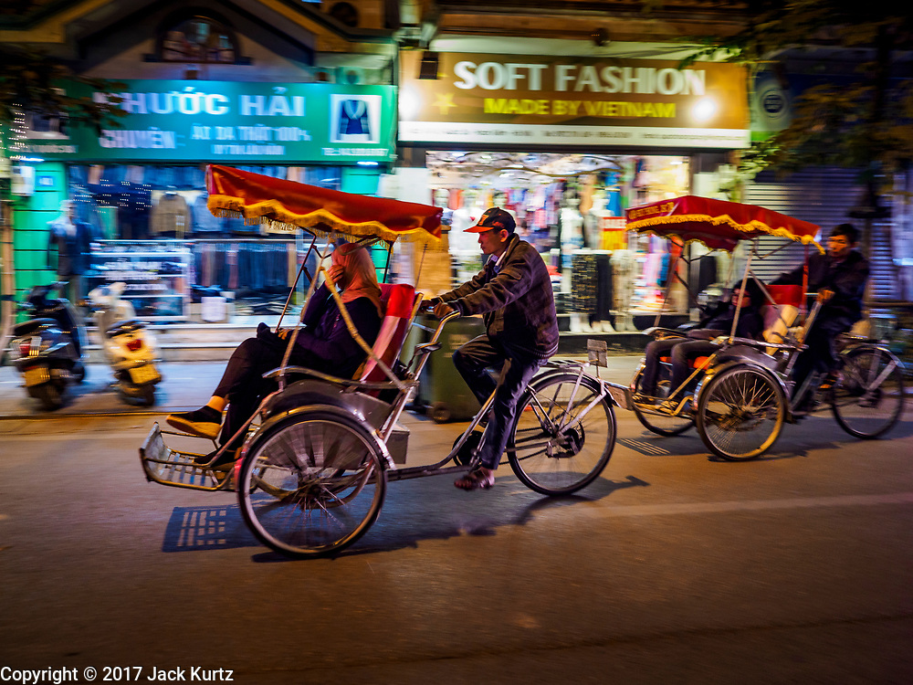 26 DECEMBER 2017 - HANOI, VIETNAM: Tourists on an evening pedicab tour of the Old Quarter of Hanoi.      PHOTO BY JACK KURTZ