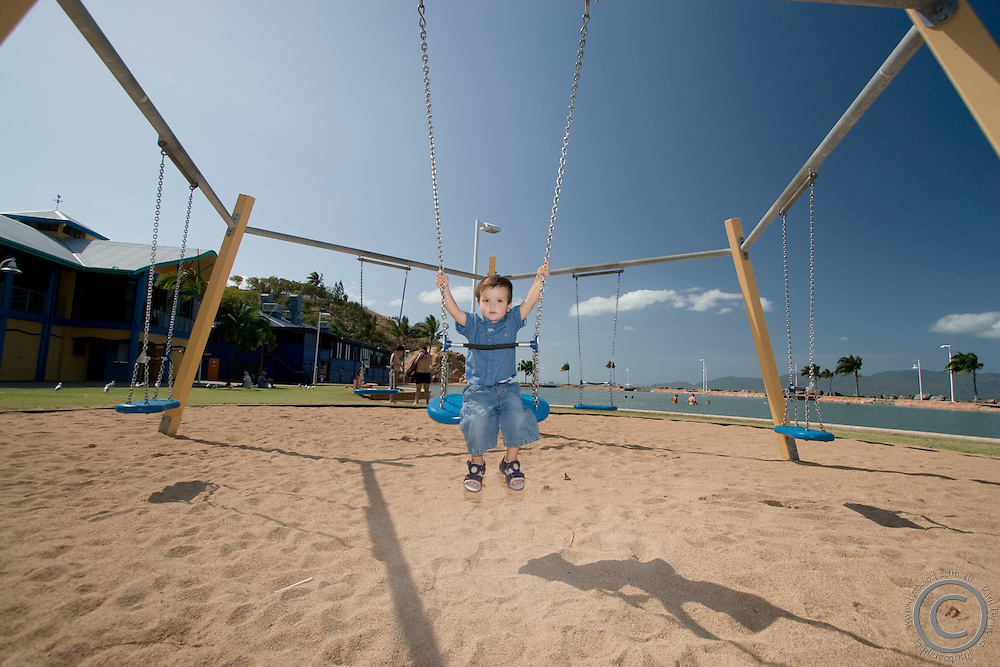 A young boy plays on a swing at the Beach on The Strand.
