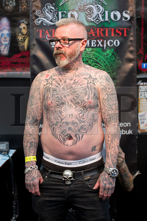 © Licensed to London News Pictures. 25/05/2013. London, UK. A man shows his tattooed chest as a tattoo artist works on his back at the Great British Tattoo Show in Alexandra Palace in London today (25/05/2013).The event, which began last year, brings tother world-class tattoo artists artists, vendors and traders and this year takes place on the 25th and 26th of May 2013. Photo credit: Matt Cetti-Roberts/LNP