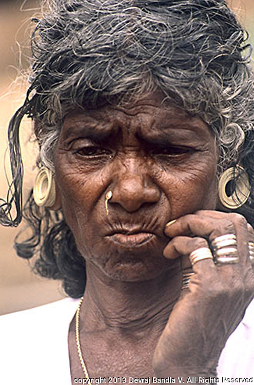 Old Pania tribal woman wearing metal rings and ear ornaments made of palm leaf.
