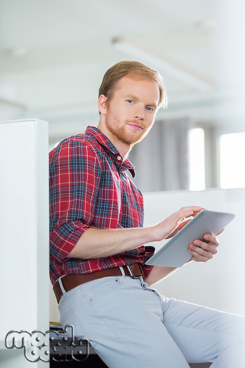 Portrait of confident businessman using tablet PC in creative office