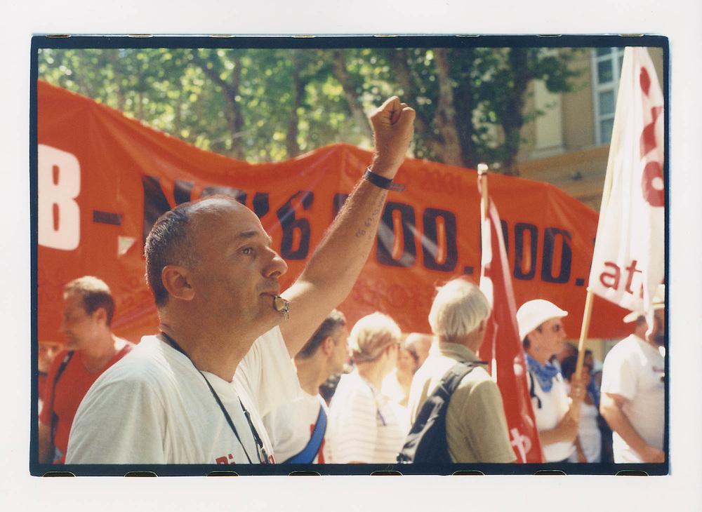 Proteste contro il summit del G8, Genova luglio 2001. Corteo di sabato 21 luglio. Un manifestante alza il pugno. Sul suo braccio, scritti con una penna, i numeri del supporto legale del Genoa Social Forum. In seguito alle centinaia di arresti del giorno prima, molti manifestanti usano questa precauzione.