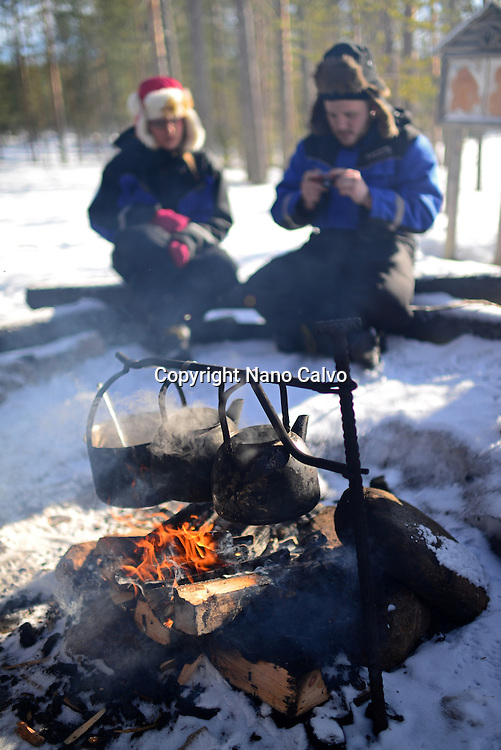 Stop for a warm drink and food, around the fire. Wilderness husky sledding taiga tour with Bearhillhusky in Rovaniemi, Lapland, Finland