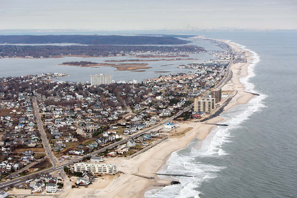 Jetties and revetments (retaining wall or facing of masonry or other material, supporting or protecting a rampart or wall) are scattered with pockets of beach erosion after storm with New York City on the horizon.