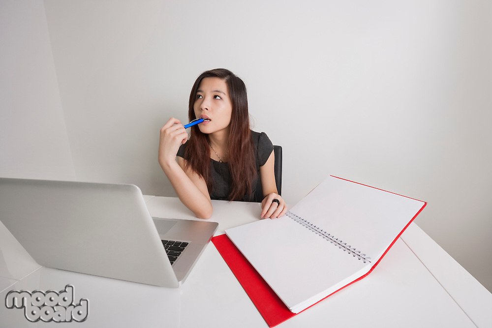 Thoughtful young businesswoman with diary and laptop at office desk