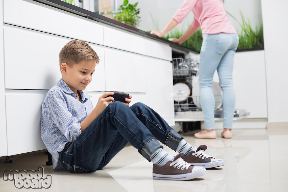 Full length of boy using hand-held video game with mother in background at kitchen
