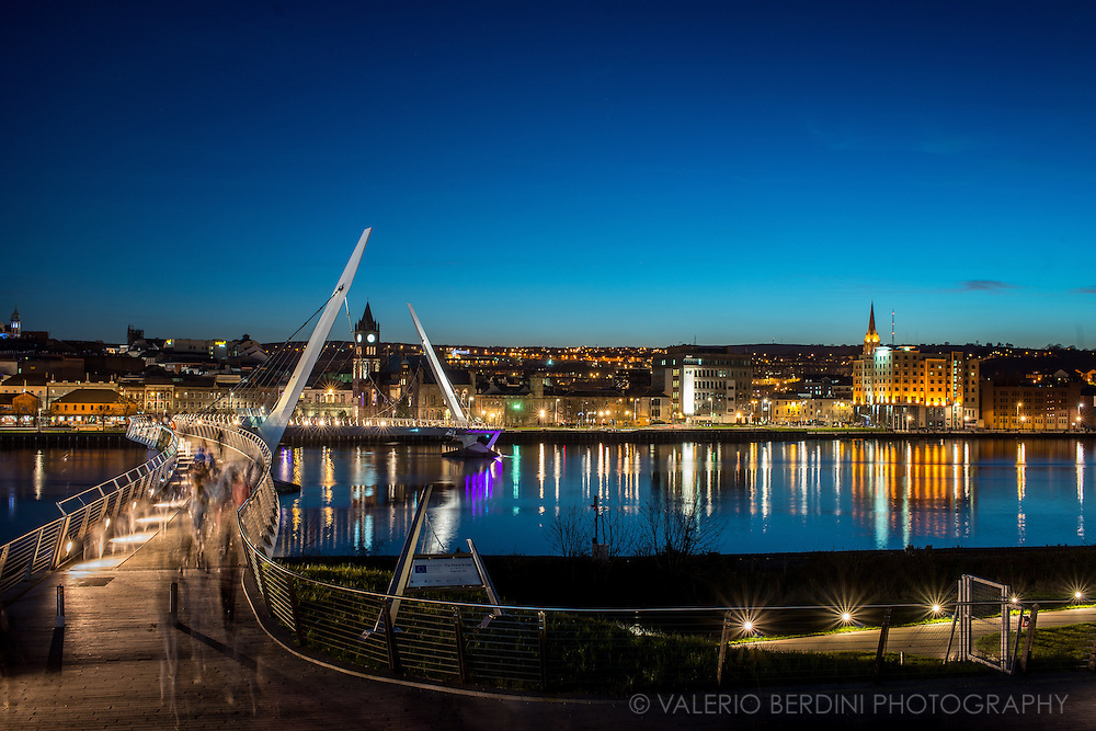 Night view of the Peace Bridge and Derry through the River Foyle. The Peace Bridge is a cycle and footbridge bridge across the River Foyle in Derry, Northern Ireland. The Peace Bridge is part of Derry/Londonderry&rsquo;s regeneration programme. Funded by the European Union&rsquo;s PEACE III programme the Peace Bridge has become an iconic structure for the city.<br /> Launched in 2011, the bridge has been embraced by citizens and has radically changed the way people perceive the city.