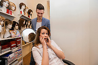 Male hairstylist showing hair to worried female customer in salon