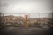 A view of the Palestinian village called Tzur Bahir, meaning Clear Rock is seen through a newly built basketball court in Har Homa. Image © Angelos Giotopoulos/Falcon Photo Agency