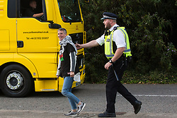 London, UK. 5 September, 2019. A Metropolitan Police officer pursues an activist along the pavement as a truck leaves ExCel London on the fourth day of a week-long carnival of resistance against DSEI, the world's largest arms fair.