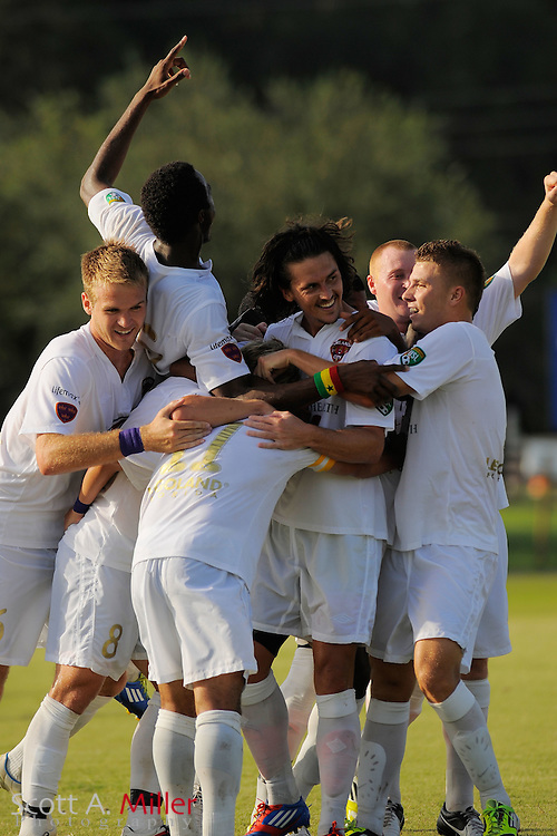 Orlando City forward Drew Helm (23) is surround by his teammates after scoring the go-ahead goal in Orlando City's 2-1 win over Laredo Heat in their PDL Southern Conference Championships playoff game at Trinity Catholic High Schooll on July 20, 2012 in Ocala, Florida. ..©2012 Scott A. Miller