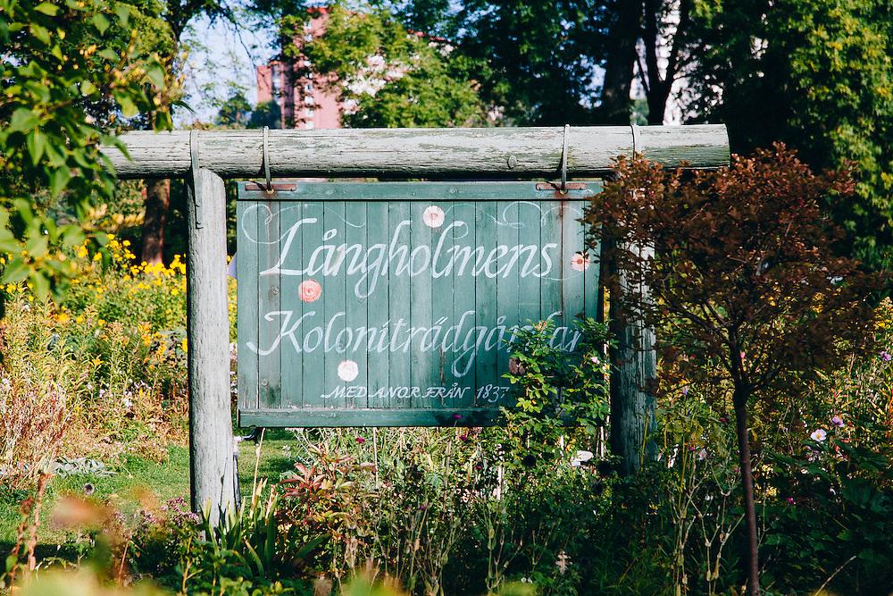 A Swedish wooden sign saying 'Långholmens Koloniträdgårdar' (community gardens or allotment gardens in English)