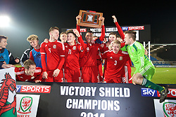 BALLYMENA, NORTHERN IRELAND - Thursday, November 20, 2014: Wales' captain Tyler Roberts lifts the Victory Shield trophy as the players celebrate after beating Northern Ireland 2-0 during the Under-16's Victory Shield International match at the Ballymena Showgrounds. Max Smallcombe, Keiron Proctor, Daniel Jefferies, Liam Cullen, captain Tyler Roberts, Ben Williams, goalkeeper Scott Coughlan. (Pic by David Rawcliffe/Propaganda)