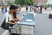 Jay Williams and Lee Bullitt, of New York, play on the piano designed by Arianna Huffington and her sister Agapi Stassinopoulos, one of the 88 Sing for Hope Pianos, supported by Chobani, Inc., at the Josie Robertson Plaza at Lincoln Center, Sunday, June 16, 2013. The event celebrates the conclusion of the Sing for Hope Pianos project, a two-week public art installation around the five boroughs of New York.  (Photo by Diane Bondareff/Invision for Sing for Hope)