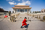 Young girl runs past a soldier outside Mao's Mausoleum, Tian'an Men Square, Beijing, China
