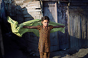In the early morning, Muskhan, 12, is playing with her scarf in front of her home by the railway tracks in New Arif Nagar, one of the water-affected colonies standing next to the abandoned Union Carbide (now DOW Chemical) industrial complex, site of the infamous 1984 gas tragedy in Bhopal, Madhya Pradesh, central India. The poisonous cloud that enveloped Bhopal left everlasting consequences that today continue to consume people's lives. Muskhan does not attend school or ay sort of practical education.