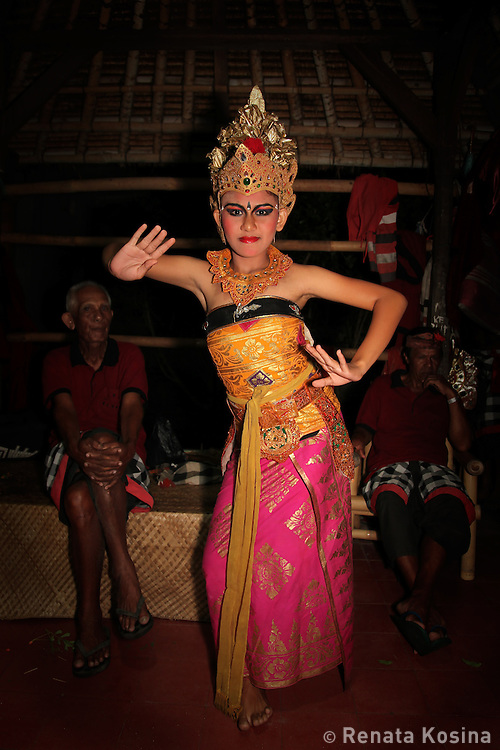 A young female Kecak dancer in Batubulan is practicing backstage before her performance. Kecak is the most unique Balinese dance in which, instead of music, 100 men chant Cak. In the 1930s Ramayana story was added to the original trance dance.