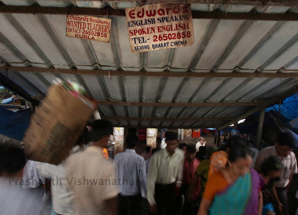 People walk past advertisements of English Speaking classes displayed on a railway bridge, in Mumbai, India, on Monday August 20, 2007. Photographer: Prashanth Vishwanathan
