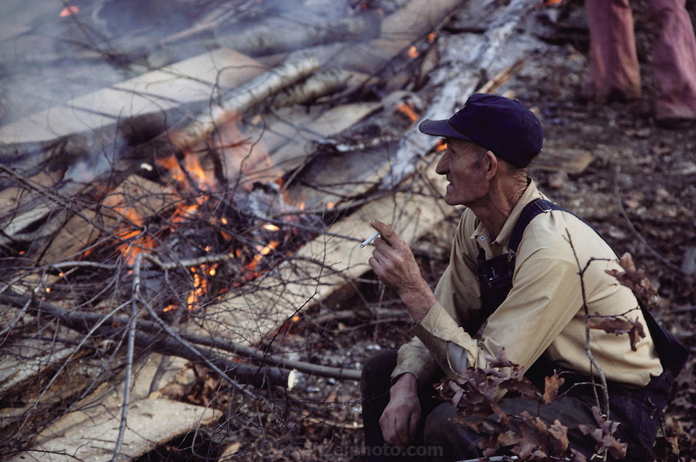 Tobacco - Clifton Walton smoking a cigarette while overseeing preparation for tobacco seedling ground by burning off oak lumber mill scraps and brush on his farm in Charlotte, Tennessee. MODEL RELEASED. USA.