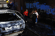 A young boy wearing his school uniform kicks the door of a burned out car that was set alight by vandals beneath the infamous Divis flats of the Catholic Lower Falls Road, West Belfast, on 7th June 1995, in Belfast, Northern Ireland, UK. The Divis Tower was a flashpoint area during the height of the Troubles. Nine year-old Patrick Rooney a child of a similar age to this lad, was the first child killed in the Troubles, killed in the tower during the Northern Ireland riots of August 1969.
