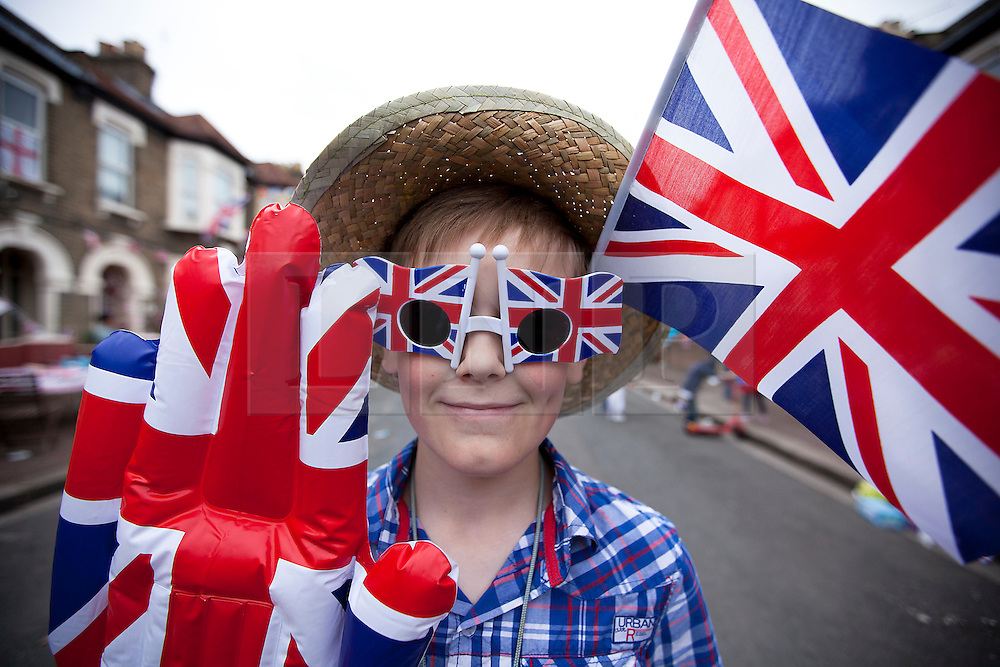 © Licensed to London News Pictures. 02/06/12. LONDON, UK. A young boy shows his patriotic spirit as he takes part in a Jubilee street party held by the residents of Ravenscroft Road in Canning Town, East London. The Royal Jubilee celebrations. Great Britain is celebrating the 60th  anniversary of the countries Monarch HRH Queen Elizabeth II accession to the throne this weekend Photo credit : LNP