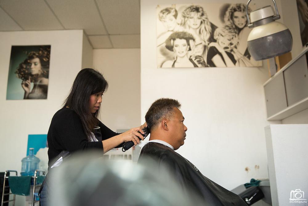 Hue Luu cuts Milpitas resident Severino Gatdula's hair at Tina's Hair Design in Milpitas, California, on September 11, 2014. (Stan Olszewski/SOSKIphoto)