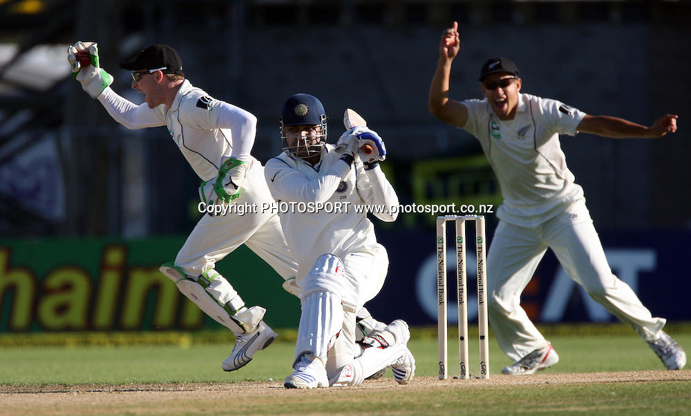 NZ wicketkeeper Brendon McCullum takes a catch to dismiss Virender Sehweg as Ross Taylor celebrates.<br />Day 2 of the 2nd test match between New Zealand and India at McLean Park, Napier, New Zealand, Friday 27 March 2009. Photo: Andrew Cornaga/PHOTOSPORT