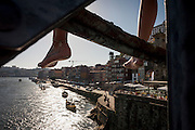 The legs of a local youth before he dives off the Ponte de Dom Luis I bridge and into the cold waters of the River Douro with the city of Porto behind on , on 20th July, in Porto, Portugal. For the price of a Euro, will the boys leap off the girders, into the water - known as tombstoning, due to its obvious dangers. The Dom Luís I (or Luiz I) Bridge is a double-decked metal arch bridge that spans the Douro River between the cities of Porto and Vila Nova de Gaia in Portugal. At the time of construction its span of 172 m was the longest of its type in the world. (Photo by Richard Baker / In Pictures via Getty Images)