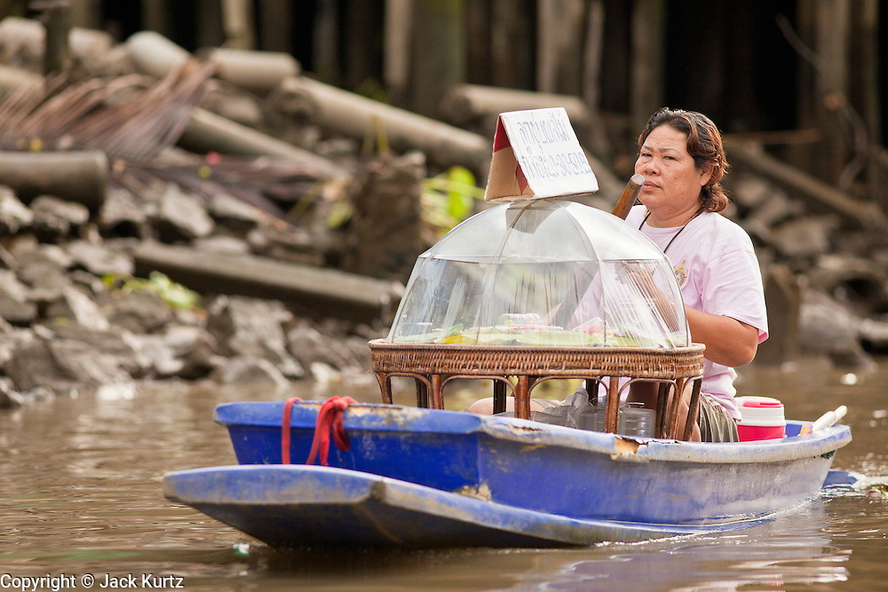 "10 JULY 2011 - AMPHAWA, SAMUT SONGKRAM, THAILAND:  A food vendor paddles her canoe along the main canal in Amphawa, Thailand, about 90 minutes south of Bangkok. The Thai countryside south of Bangkok is crisscrossed with canals, some large enough to accommodate small commercial boats and small barges, some barely large enough for a small canoe. People who live near the canals use them for everything from domestic water to transportation and fishing. Some, like the canals in Amphawa and nearby Damnoensaduak (also spelled Damnoen Saduak) are also relatively famous for their ""floating markets"" where vendors set up their canoes and boats as floating shops.     PHOTO BY JACK KURTZ"