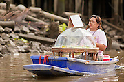 """10 JULY 2011 - AMPHAWA, SAMUT SONGKRAM, THAILAND:  A food vendor paddles her canoe along the main canal in Amphawa, Thailand, about 90 minutes south of Bangkok. The Thai countryside south of Bangkok is crisscrossed with canals, some large enough to accommodate small commercial boats and small barges, some barely large enough for a small canoe. People who live near the canals use them for everything from domestic water to transportation and fishing. Some, like the canals in Amphawa and nearby Damnoensaduak (also spelled Damnoen Saduak) are also relatively famous for their """"floating markets"""" where vendors set up their canoes and boats as floating shops.     PHOTO BY JACK KURTZ"""