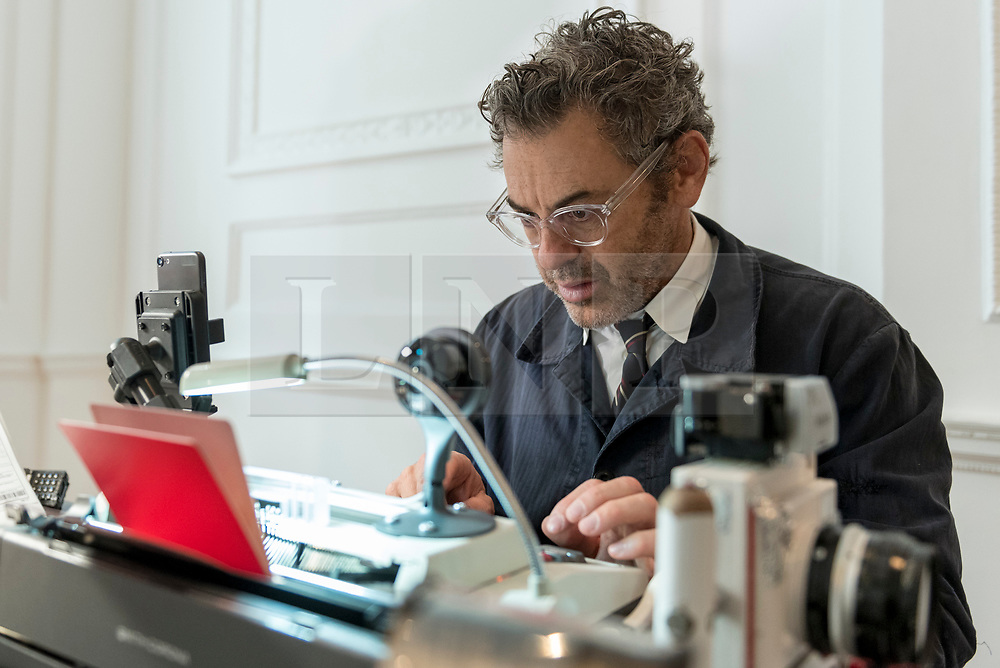"""© Licensed to London News Pictures. 05/10/2018. LONDON, UK. Tom Sachs issues a passport. Preview of """"Swiss Passport Office"""" by American artist Tom Sachs at Galerie Thaddaeus Ropac in Mayfair.  To coincide with Frieze Week, the gallery will remain open for 24 hours from 6pm 5 October to 6pm 7 October for the issuing of serial-numbered Tom Sachs Swiss passports for visitors.  The installation reflects the concerns relating to Brexit, Syria and Donald Trump's immigration policies and challenges the notion of global citizenship.  Photo credit: Stephen Chung/LNP"""