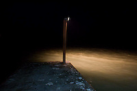 A light on a wooden post lights up water from a dock at Hotel La Pesca in La Pesca, Mexico.
