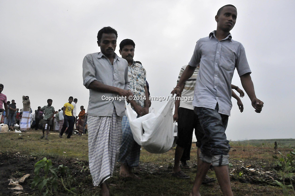 61530157<br /> Rescuers carry bodies after the ferry accident in Munshiganj district, Dhaka, Bangladesh, May 16, 2014. Bangladesh rescuers have dragged out 10 more bodies, raising the death toll to 22 in the ferry accident on river Meghna, after it sank in storm on Thursday afternoon,  Friday, 16th May 2014. Picture by  imago / i-Images<br /> UK ONLY