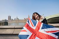 Portrait of happy woman holding British flag against Big Ben at London; England; UK