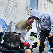 Day three of the occupation - and the first Monday. A women is keeping the square clean. The square has been renamed Tahrir Square after the square in Cairo. The Occupy London Stock Exchange movement was formed in London in solidarity with the US based Occupy Wall Street. The movements are a respons and in anger to what is seen by many as corporate greed and a failed banking system being bailed out by the public, - which in return are suffering austerity measures to make up for the billions of lost money. The movement occupied the St Paul's Square in the City of London Sat Oct 15 after it failed to secure and occupy Pator Noster Square and the Stock Exchnage itself.