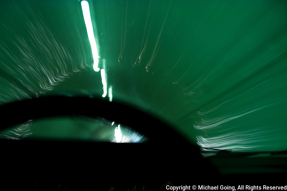 Car steering wheel silhouetted against motion blurred 2nd Street Tunnel in downtown Los Angeles.With light streaks and light trails.
