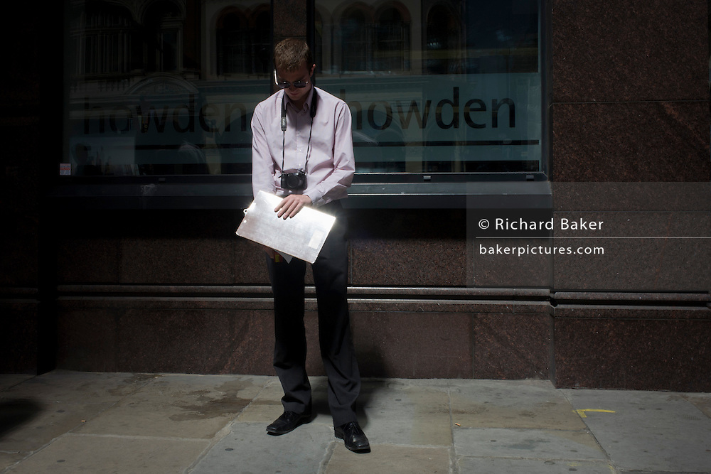 An anonymous official takes spot measurements of extreme heat from the Walkie-talkie building as Londoners experience the unexpected intensity of localised solar rays, reflected off the concave plate glass windows of one of the capital's newest skyscrapers. The hotspot has surprised developers and passers-by below and which has already melted a parked car and left soft street fittings smouldering in Eastcheap Street, City of London, the capital's financial district. Thermometers placed in the street reached 144F (62 celsius) and city workers poured out of their offices at lunchtime to witness the strange phenomena of intense, Biblical light and blistering heat.