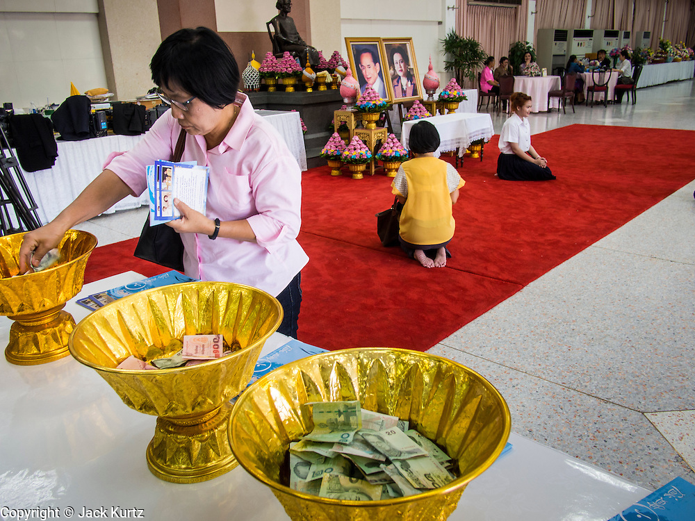 01 AUGUST 2013 - BANGKOK, THAILAND: A woman donates money to Siriraj Hospital while people pray in front of photos of Bhumibol Adulyadej, the King of Thailand, and his wife, Queen Sirikit, who have both been living in Siriraj Hospital. The King, 85, was discharged from the hospital, Thursday where he has lived since September 2009. He traveled to his residence in the seaside town of Hua Hin, about two hours drive south of Bangkok, with his wife, 80-year-old Queen Sirikit, who has also been treated in the hospital for a year.       PHOTO BY JACK KURTZ