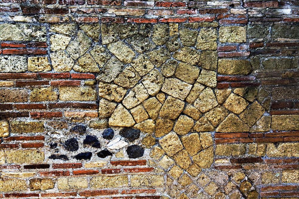 Herculaneum : wall structure with variety of patterned stones & bricks forming a pleasant abstract design.