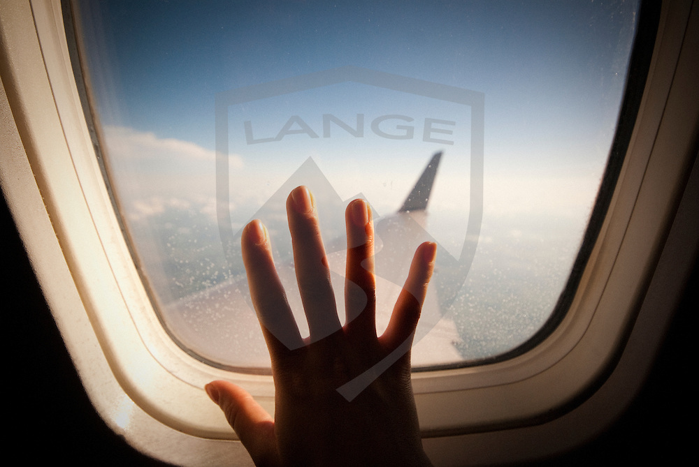 airborne woman's hand on airplane window.