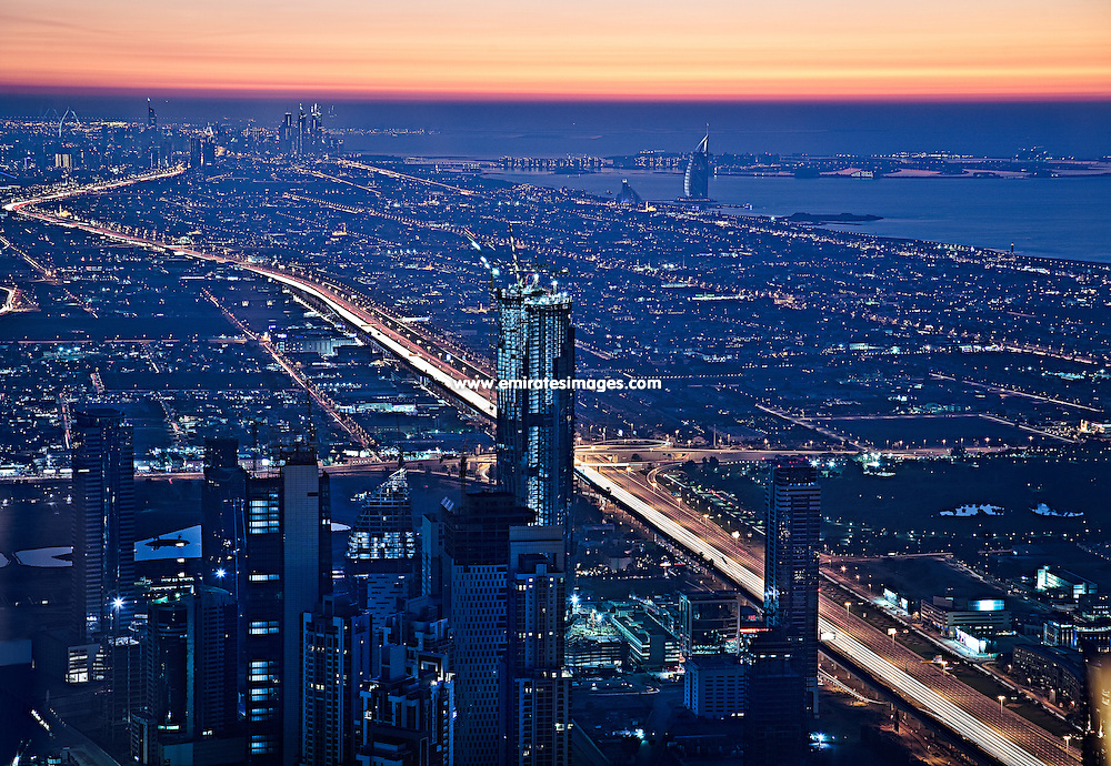 View of Dubai at sunset from Burj Khalifa. The photo is taken from the observation deck, At The Top. In the background, the distinctive Burk Al Arab hotel can be seen, as well as The Palm Jumeirah and Dubai Marina.