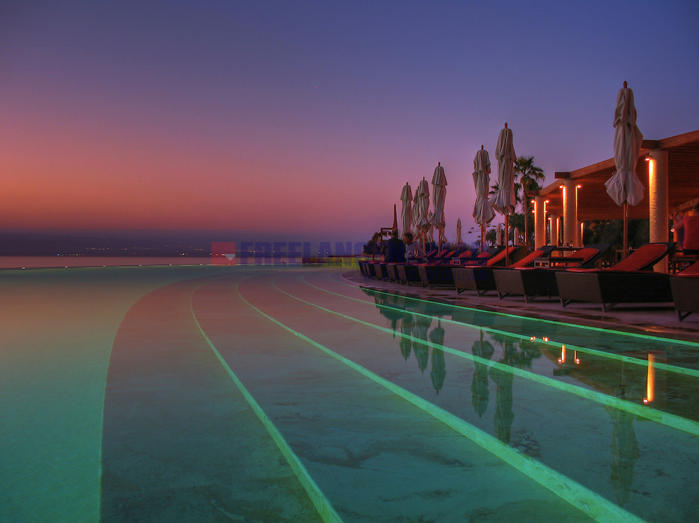 Kempinski Ishtar Dead Sea luxury hotel resort infinity pool view during colorful sunset over west bank of Jordan