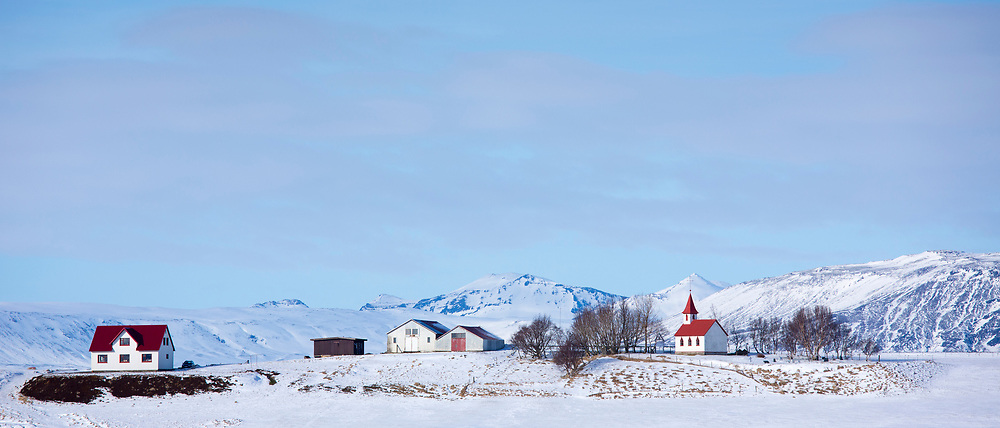 Quaint hamlet village and church Braedratungukirkja with typical traditional red roof in snowy landscape in Iceland
