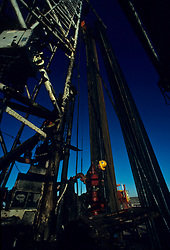 Stock photo of a worker standing at the base of an on-shore rig