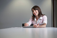 Woman sitting behind desk writing notes