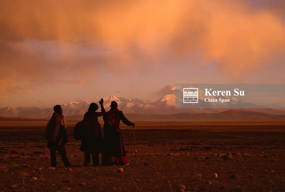 Tibetan pilgrims praying on the high plateau with Peak Namunani in the distance at sunset, Tibet, China